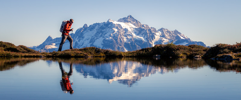 Whatcom, Yellow Aster Butte - Hiker passing small tarn with Mt. Shuksan reflected, panoramic