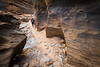 Zion, Clear Creek - Woman navigating icy section in slot canyon