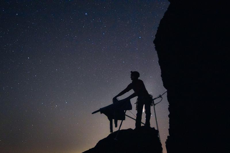 Columbia, Vantage - Rock climber ironing his shirt on top of rock with comet between legs
