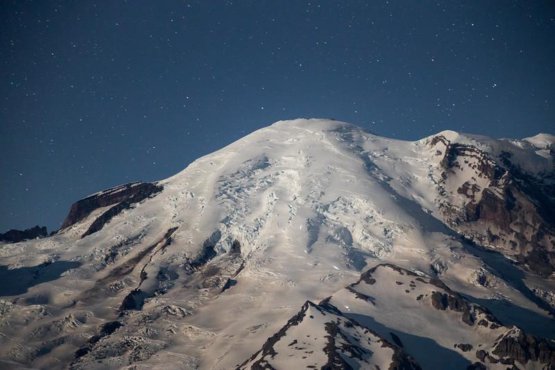 Rainier, Sunrise - Close up of summit of Rainier under bright moonlight with climbers
