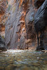 Zion, The Narrows - Two tiny hikers beneath huge rock formations, vertical