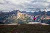 Rainy Pass, Cutthroat Pass - Woman hiker on cliff overlooking Hinkhouse Peak and distant larch trees