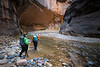 Zion, The Narrows - Two hikers entering large alcove