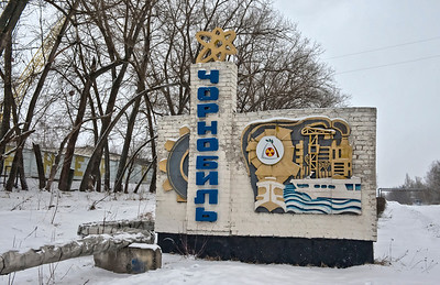 The Welcome Sign outside Chernobyl, Ukraine.  After the accident they installed new water pipes rather than use the old ones buried under irradiated ground. And instead of disturbing the soil, they laid them above ground. Note the pipe that crosses over the road, in the distance on the right.