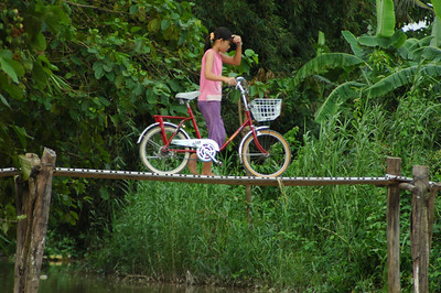 Girl with bicycle, Mekong delta region, Vietnam.