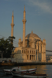 Detail of small boats near the waterfront Ortakoy Mosque, built in 1853 - 1854, and the Bosphorus Bridge, completed in 1973, connecting Europe (near side) with Asia, in Istanbul, Turkey.