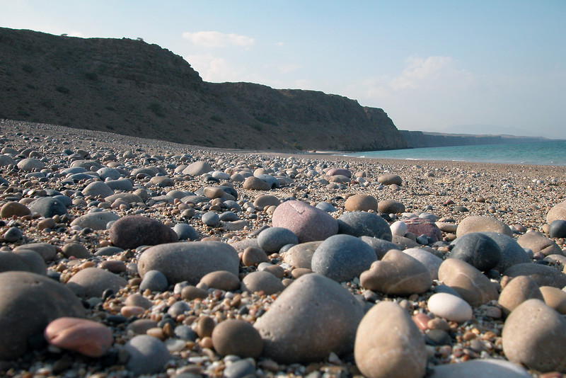 Pebbly beach and limestone cliffs north of Dibab, Oman