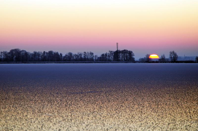 Winter sunrise over frozen lake, The Netherlands