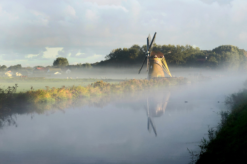 Misty sunrise at windmill 'Hoop Doet Leven' along the Haarlem - Leiden canal near the village of Voorhout, The Netherlands