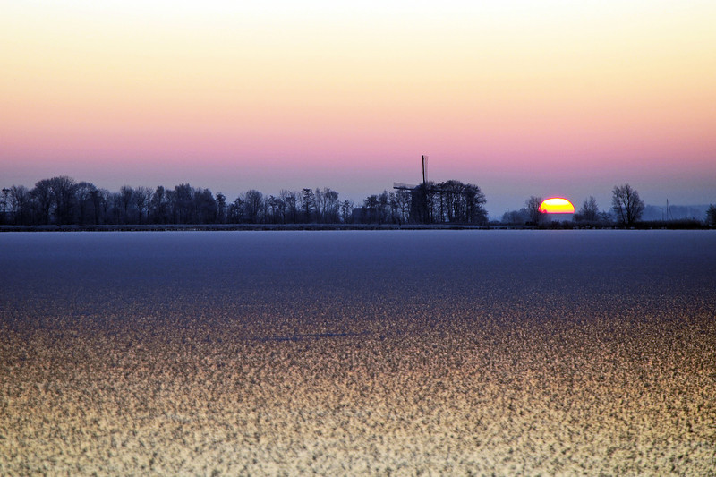 Winter sunrise over frozen lake, The Netherlands