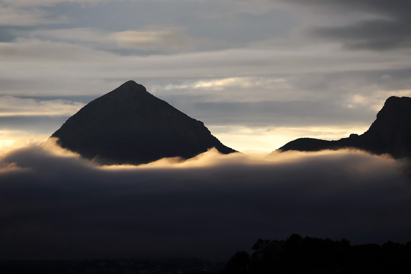 Coastal fog moving inland over Altea, with the Puig Campana mountain rising above it, Spain