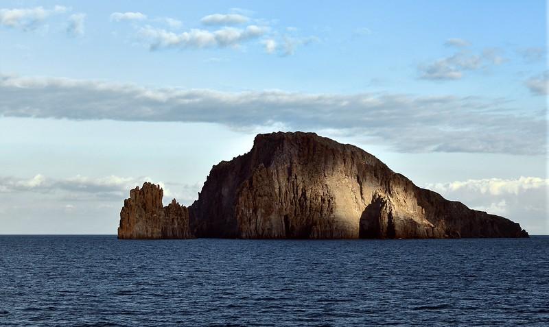Sunbeams striking the volcanic cliffs of Basiluzzo island in the Eolian archipelago, Italy