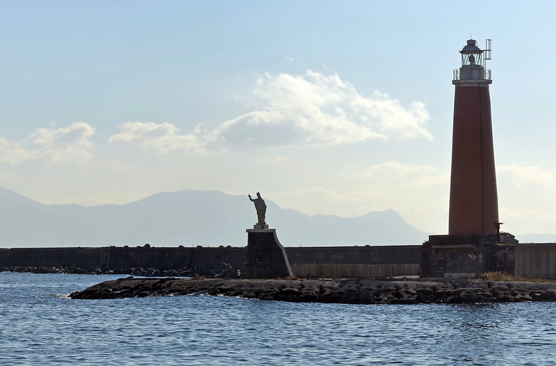 Lighthouse and San Gennaro statue on the San Vicenzo breakwater of Naples' harbour, Italy