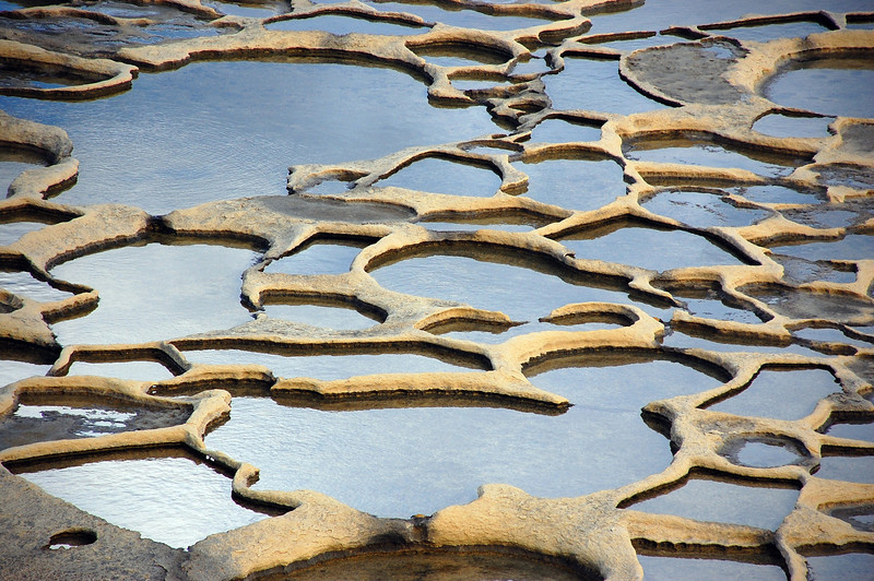 Salt pans in the coastal cliffs of Gozo, Malta