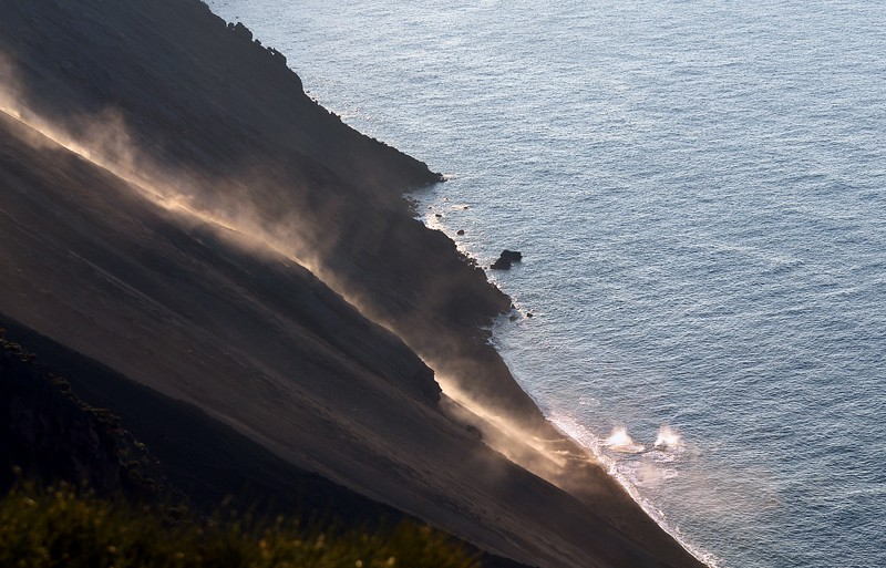 Fresh volcanic bombs rolling along the steep Sciara del Fueco slope of the Stromboli volcano into the sea, Italy