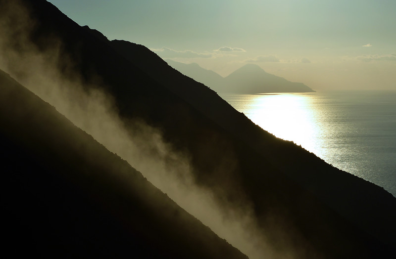 Smoking steep volcanic slope of Sciara del Fuoco on Stromboli, with the island of Salina in the background
