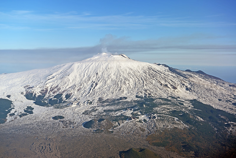 Smoking summit of Etna volcano (3329 m) on the island of Sicily in Italy, with numerous historic lava flows and side vents clearly standing out in the snow cover along its vast slopes