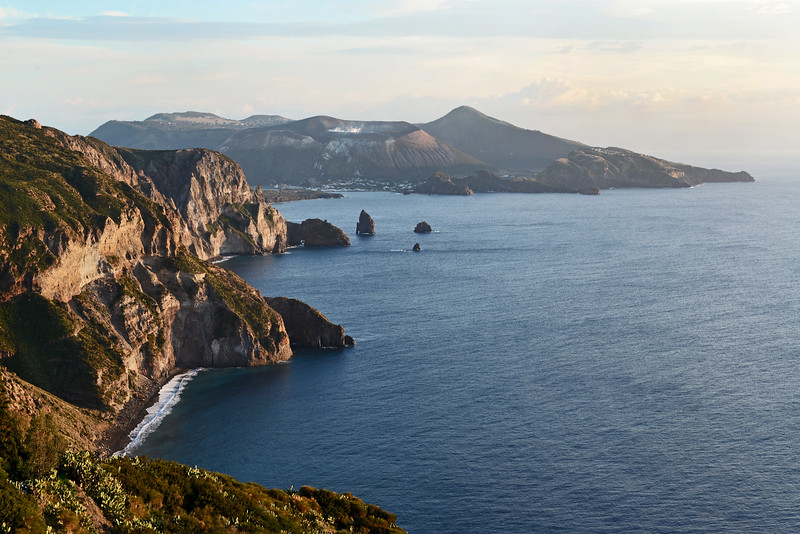 Lipari's steep southwestern cliffs at Valle Muria, with the smoking crater and older caldera of Vulcano island in the background, Italy