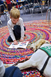 Caden Cornish reads a book to therapy dog Zeus during a vist to the 1st grade classroom Jan. 9 at All Saints Catholic School.