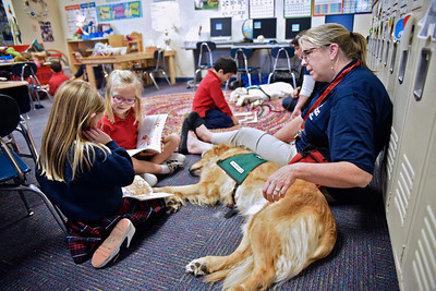 Sloan Grant, at left, and Sophia Whitney read to Sumo as he rests with Bridget Bronson during a visit to the 1st grade Jan. 9 at All Saints Catholic School.