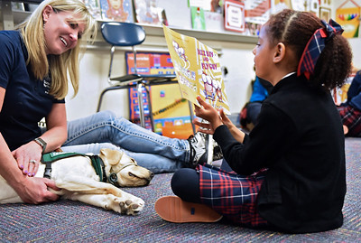 Soleil Szpernalowski shows therapy dog ?? the pictures in a book during a visit to the 1st grade at All Saints Catholic School Jan. 9.