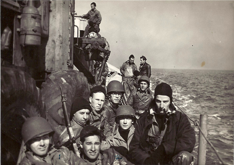 Invasion barge on the way to Cat Island, Jan. 1944.  McKee is the fella real close with the helmet.Schumaker with the stocking cap.  Carey between 'Manny' and Murtaugh, the photographer.  Behind 'Manny' is Nick, then Ward with the helmet.  Way back is Reiman (possibly Reaman).  We're sitting beside a road grader.