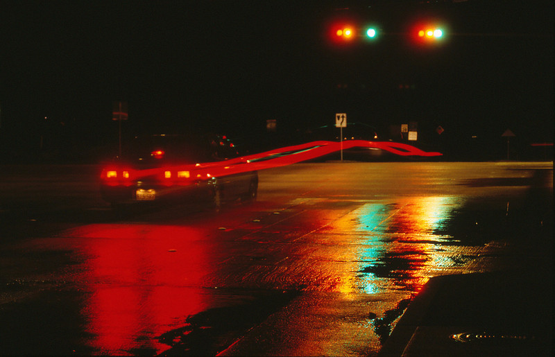 Car backing up througth a light at an intersection  - capturing the light trail
