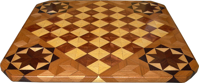 """Cbd Hb-Bub with Star 3<br />   This chessboard is 11 3/4"""" square. Over all the board is 17 ¼"""" square. Each square is just under 1 1/2"""" and is made with 4 triangles.  Two types of wood are in the chessboard. six kinds of wood are on the whole board.  The dark square is """"Bubinga"""" from West Africa; the light square is """"Hackberry"""" from Missouri. """"Elm"""" from Missouri is around the chessboard itself. The design in each corner is a variation of a """"Rolling Star"""" quilt pattern. The wood on it, from the center of the star is """"Walnut"""" and """"Maple"""" from Missouri, """"Wenge"""" from West Africa and then the """"Elm"""". There are 560 pieces in the over lay, using 6 kinds of wood.<br /> <br /> Also on the back, I signed it, listed the wood, and dated it. After the date the words """"Foot Cut"""" let you know I made it on my foot powered table saw. <br />   <br />    This gives a completely different look to a chessboard.  When not being used as a chessboard, it is made to hang on the wall from one corner.  They make a very beautiful wall hanging."""