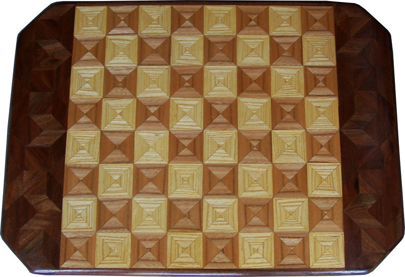 "Cbd 12X18 Elm-Ash-Wal <br /> This chess board is 12"" square, 12 ½"" X 17 ½"" over all.  Each square is 1 ½"" and is made using 4 triangles.  Three kinds of wood are on the chess board.  The dark square is ""Elm""; the light square is ""Ash"", ""Walnut"" is around the chessboard, all from Missouri. There are 418 pieces in the over lay.<br /> <br />     On the back, I signed it, listed the wood, and dated it.<br /> <br />    I tried to match the grain on most of the squares which gives it a unique look.  <br />   <br />   This gives a completely different look to a chess board.  When not being used as a chess board, it is made to hang on the wall.  They make a very beautiful wall hanging."