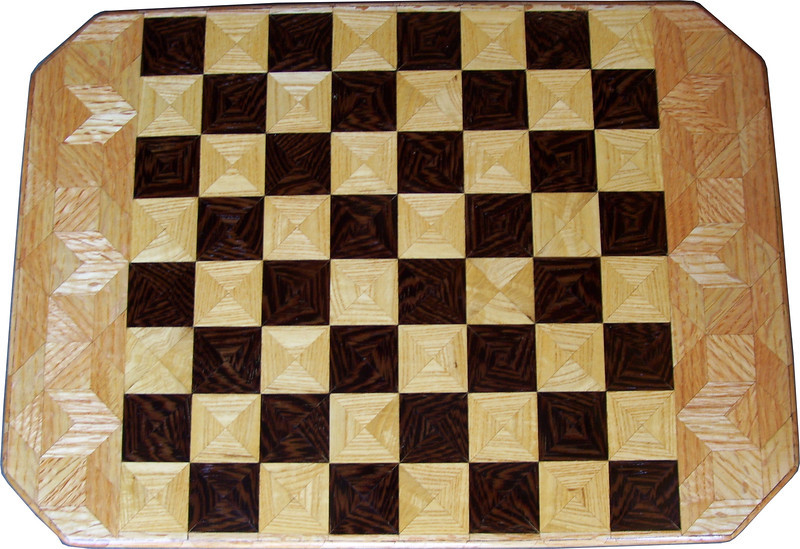 "Cbd 12X18 Wenge-Ash-Oak <br /> This chess board is 12"" square, 12 ½"" X 17 ½"" over all.  Each square is 1 ½"" and is made using 4 triangles.  Three kinds of wood are on the chess board.  The dark square is ""Wenge"" from West Africa; the light square is ""Ash"", ""Oak"" is around the chessboard, both from Missouri. There are 432 pieces in the over lay.<br /> <br />    On the back, I signed it, listed the wood, and dated it.  <br />   <br />   This gives a completely different look to a chess board.  When not being used as a chess board, it is made to hang on the wall.  They make a very beautiful wall hanging."
