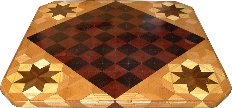 """Cbd Ph-Wenge With Star 4<br />    This chess board is 11 3/4"""" square. Over all the board is 17 ¼"""" square. Each square is just under 1 1/2"""" and is made with 4 triangles.  Two types of wood are in the chessboard. Five kinds of wood are on the whole board.  The dark square is """"Wenge"""" from West Africa; the light square is """"Purpleheart"""" from Central or South America. The design on the corners is a variation of a """"Rolling Star"""" quilt pattern. From the star out is """"Walnut"""" """"Hackberry"""" and """"Elm"""" from Missouri. There are 560 pieces in the over lay using five kinds of wood.<br /> <br />   Also on the back, I signed it, listed the wood, and dated it. After the date the words """"Foot Cut"""" let you know I made it on my foot powered table saw."""