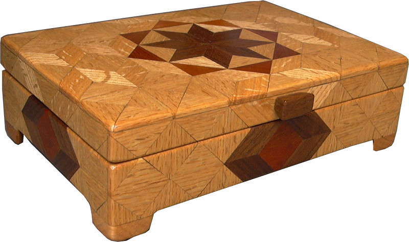 """Flat Oak <br /> I call this my Flat """"Oak"""" Box. On the top of the box is a variation of a """"Rolling Star"""" quilt pattern.  The flat box is about 9 1/4"""" x 6 1/4"""" and 2 7/8"""" high on the outside. Inside it is 8 1/2"""" x 5 1/2"""" x 1 3/8"""".  I made it using 238 pieces of wood cut in either diamond or triangle shapes from different kinds of wood. The box is finished in its natural color with 5 or 6 coats of a clear wiping varnish, rubbed in by hand. The pieces are a bit over 3/16"""" thick, glued onto a Baltic Birch base, so hold up much better than a thin veneer.<br /> The type of wood is listed on the bottom of the box from the center out. On this box the wood is """"Walnut"""" and """"Oak"""" from Missouri and """"Brazilwood"""" from Brazil.<br />     On the bottom I signed it, listed the wood, and dated it.  After the date, the words """"Foot Cut"""" let you know I made it on a foot powered table saw.<br />  <br /> I lined the box with black velveteen."""