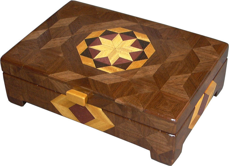 """Flat Bright<br /> I call this my Flat """"Bright"""" Box. On the top of the box is a variation of a """"Rolling Star"""" quilt pattern.  The flat box is about 9 1/4"""" x 6 1/4"""" and 2 7/8"""" high on the outside. Inside it is 8 1/2"""" x 5 1/2"""" x 1 3/8"""".  I made it using 254 pieces of wood cut in either diamond or triangle shapes from different kinds of wood. I used the half size pieces for the """"Rolling Star"""" on the top, so there are 32 pieces where I would normally have 16 pieces. The box is finished in its natural color with 5 or 6 coats of a clear wiping varnish, rubbed in by hand. The pieces are a bit over 3/16"""" thick, glued onto a Baltic Birch base, so hold up much better than a thin veneer.<br /> The type of wood is listed on the bottom of the box from the center out. On this box the wood is """"Hackberry"""" from Missouri, """"Purpleheart"""" from Central or South America, """"Wenge"""" from West Africa, """"Satinwood"""" from Sri Lanka and """"Walnut"""" from Missouri.<br />  I made this box in 1998. On the bottom I signed it, listed the wood, and dated it.  After the date, the words """"Foot Cut"""" let you know I made it on a foot powered table saw.<br />  <br /> I lined the box with black velveteen."""