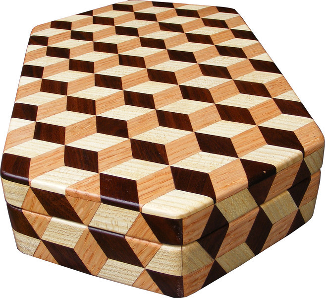 """Large Hexagon Tumbling Block Box, view 2<br /> The large hexagon box is based on the """"Tumbling Block"""" quilt pattern. It measures 7 ¼"""" X 13 3/8"""" and 2 3/8"""" high. Inside measurements are 6 ¼"""" X 12 ¼"""" X 1 ½"""".  There are 304 pieces on the overlay. The pieces are cut and glued in place, one piece at a time. The pattern covers the top and extends over the edge uninterrupted, to the bottom. The box is finished in its natural color with 5 or 6 coats of a clear wiping varnish, rubbed in by hand. The pieces are a bit over 3/16"""" thick, glued onto a Baltic Birch base.<br /> <br /> This box is made from Hackberry, Oak, and Walnut, all native to Missouri. I lined the box with black velveteen.<br /> <br /> The pattern has the illusion of a lot of blocks but there are as many stars as there are blocks. The design forces you to see the blocks. On each diamond, if you go to the side you are in the middle of a block. At each point you are in the middle of a star that has 6 points."""
