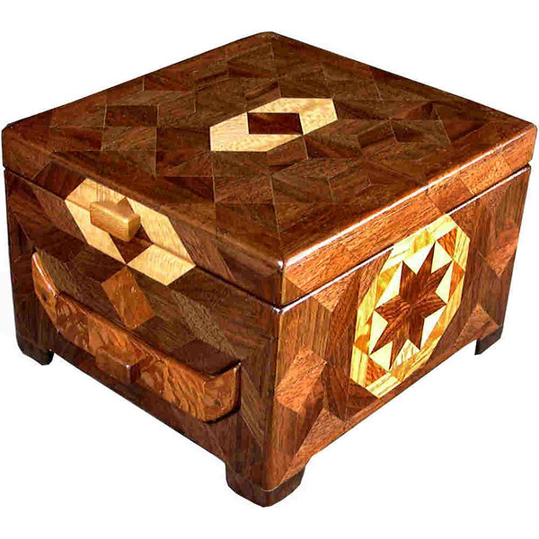 """1 Drawer Brown Tone <br />   I call this my """"Brown Tone 1 Drawer Cabinet"""". On the sides and back of the cabinet is a variation of a """"Rolling Star"""" quilt pattern, in two sizes. On the sides I have 32 pieces in the same area that I have 16 pieces on the back.  The cabinet is about 5 ½ """"tall x 7 1/4"""" wide and 8"""" front to back. I made it using about 378 pieces of wood cut in either diamond or triangle shapes from different kinds of wood. I used the half size pieces for the """"Rolling Star"""" on the sides, so there are 32 pieces where I would normally have 16 pieces. The cabinet is finished in its natural color with 5 or 6 coats of a clear wiping varnish, rubbed in by hand. The pieces are a bit over 3/16"""" thick, glued onto a Baltic Birch base, so they hold up much better than a thin veneer.<br />   The type of wood is listed on the bottom of the cabinet, from the center out of the """"Rolling Star"""" quilt pattern on the side or back. On this cabinet the wood is """"Chechen"""" from Mexico, """"Sycamore"""" from Missouri, """"Lacewood"""" from Australia, """"Oak"""" and """"Walnut"""" from Missouri.<br />   The drawer design of the jewelry cabinet makes it unique from all others. The type of wood on the drawer front is listed on the inside of the drawer front along with the number of the cabinet. The number of the cabinet is also listed on the inside on the back. You will see it when you pull the drawer out and look inside at the back. The number of this cabinet is #30. I help hold the drawer together using pegs I make from the same type of wood that is on the drawer face.<br /> <br />   I made this cabinet in 1998. On the bottom I signed it, listed the wood, and dated it.  After the date, the words """"Foot Cut"""" let you know I made it on a foot powered table saw. The drawer is cut out on a scroll saw I made to go on the power supply that runs the table saw.<br />  <br />   I lined inside the top and the drawer bottom with black velveteen."""