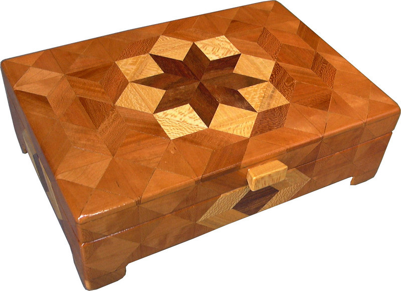 "Flat Cherry <br />   I call this my Flat ""Cherry"" Box. On the top of the box is a variation of a ""Rolling Star"" quilt pattern.  The flat box is about 9 1/4"" x 6 1/4"" and 2 7/8"" high on the outside. Inside it is 8 1/2"" x 5 1/2"" x 1 3/8"".  I made it using 238 pieces of wood cut in either diamond or triangle shapes from different kinds of wood. The box is finished in its natural color with 5 or 6 coats of a clear wiping varnish, rubbed in by hand. The pieces are a bit over 3/16"" thick, glued onto a Baltic Birch base, so hold up much better than a thin veneer.<br />     The type of wood is listed on the bottom of the box from the center out. On this box the wood is ""Chechen"" from Mexico, ""Sycamore"" and ""Cherry"" from Missouri.<br />      On the bottom I signed it, listed the wood, and dated it.  After the date, the words ""Foot Cut"" let you know I made it on a foot powered table saw.<br /> <br />      I lined the box with black velveteen."