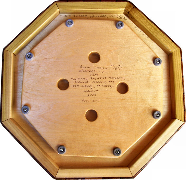 """Medium with Hachberry Lazy Susan, Bottom<br />      This is the bottom of my """"Medium with Hackberry"""" Lazy Susan. The measurements are 15 1/2"""" across (17"""" tip to tip) and 2"""" high. This lazy susan has 9 kinds of wood, all the natural colors. There are 464 pieces in the overlay, 136 diamonds and 328 triangles. The type of wood used is listed on the bottom from the center out. On this lazy susan, starting from the center is """"Tulipwood"""" from Brazil, a member of the rosewood family. """"Philippine Mahogany"""" from the Philippines, """"Lacewood"""" from Australia, """"Chechen"""" from Mexico, """"Oak"""" and """"Elm"""" from Missouri, """"Wenge"""" from West Africa, """"Hackberry"""" and """"Walnut"""" from Missouri,                  <br /> <br />      The pattern is based on the """"Lone Star"""" quilt pattern. The design extends over the edge to within ¼"""" of the table top it sits on. The stationary base is hidden on the inside, behind the edge.<br /> <br />      On the bottom I signed it, listed the wood, and dated it. After the date the words """"Foot Cut"""" let you know I made it on my foot powered table saw."""