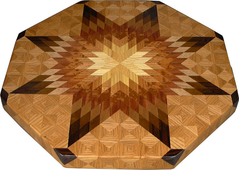 """LS Lg Oak 1<br />    This is my """"Large Oak"""" Lazy Susan.  The measurements are 19"""" across (21"""" tip to tip) and 2"""" high.  This lazy susan has 9 kinds of wood, all the natural colors.  There are 656 pieces in the overlay, 208 diamonds and 448 triangles.  The type of wood used is listed on the bottom from the center out.  On this lazy susan, starting from the center is """"Ash"""", """"Hackberry"""", and """"Oak"""" from Missouri, """"Lacewood"""" from Australia, """"Bubinga"""" from West Africa, """"Philippine Mahogany"""" from the Philippines, """"Imbuia"""" from Brazil, """"Ziricote"""" from Central America, """"Wenge"""" from West Africa, and again """"Oak"""" from Missouri.<br /> <br />    The pattern is based on the """"Lone Star"""" quilt pattern.  The design extends over the edge to within ¼"""" of the table top it sits on.  The stationary base is hidden on the inside, behind the edge."""