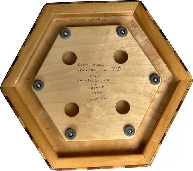 """Small Brown Tone Tumbling Block Lazy Susan, Bottom<br />     This is the bottom of the Lazy Susan<br /> <br />   The Small Brown Tone """"Tumbling Block"""" Lazy Susan is based on the """"Tumbling Block"""" quilt pattern.  It measures 12"""" across (13 ½"""" tip to tip) and 2"""" high.  There are 312 pieces on the overlay.  The pieces are cut and glued in place, one piece at a time.  The pattern covers the top and extends over the edge uninterrupted, to within ¼"""" of the table top it sits on.  The stationary base is hidden on the inside, behind the edge.  <br /> <br />   The pattern has the illusion of a lot of blocks but there are as many stars as there are blocks. The design forces you to see the blocks.  On each diamond, if you go to the side you are in the middle of a block.  At each point you are in the middle of a star that has 6 points.  <br /> <br />   This lazy susan is made from """"Hackberry, Oak, and Walnut, all native to Missouri.<br /> <br />    On the bottom, I signed it, listed the wood, and dated it.  After the date the words """"Foot Cut"""" let you know I made it on a foot powered table saw."""
