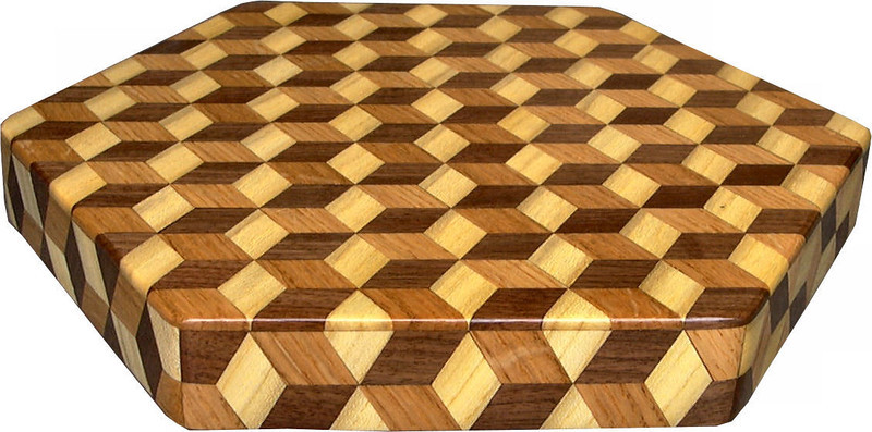 """Small Brown Tone Tumbling Block Lazy Susan<br />   The Small Brown Tone """"Tumbling Block"""" Lazy Susan is based on the """"Tumbling Block"""" quilt pattern.  It measures 12"""" across (13 ½"""" tip to tip) and 2"""" high.  There are 312 pieces on the overlay.  The pieces are cut and glued in place, one piece at a time.  The pattern covers the top and extends over the edge uninterrupted, to within ¼"""" of the table top it sits on.  The stationary base is hidden on the inside, behind the edge.  <br /> <br />   The pattern has the illusion of a lot of blocks but there are as many stars as there are blocks. The design forces you to see the blocks.  On each diamond, if you go to the side you are in the middle of a block.  At each point you are in the middle of a star that has 6 points.  <br /> <br />   This lazy susan is made from """"Hackberry, Oak, and Walnut, all native to Missouri.<br /> <br />    On the bottom, I signed it, listed the wood, and dated it.  After the date the words """"Foot Cut"""" let you know I made it on a foot powered table saw."""