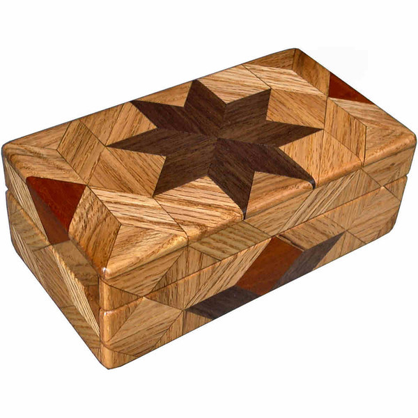 """Oak Glasses Box<br /> I call this my """"Oak"""" Glasses Box. On the top of the box is a variation of a """"Rolling Star"""" quilt pattern.  The glasses box is about 3 1/2"""" x 6 1/2"""" and 2 1/4"""" high on the outside. Inside it is 2 3/8"""" x 5 3/8"""" x 1 1/2"""".  I made it using 116 pieces of wood cut in either diamond or triangle shapes from different kinds of wood. The box is finished in its natural color with 5 or 6 coats of a clear wiping varnish, rubbed in by hand. The pieces are a bit over 3/16"""" thick, glued onto a Baltic Birch base, so they hold up much better than a thin veneer.<br />   The type of wood is listed on the bottom of the box from the center out. On this box the wood is """"Walnut"""" and """"Oak"""" from Missouri and """"Brazilwood"""" from Brazil.<br />  On the bottom I signed it, listed the wood, and dated it.  After the date, the words """"Foot Cut"""" let you know I made it on a foot powered table saw.<br />  <br />  I lined the box with black velveteen."""