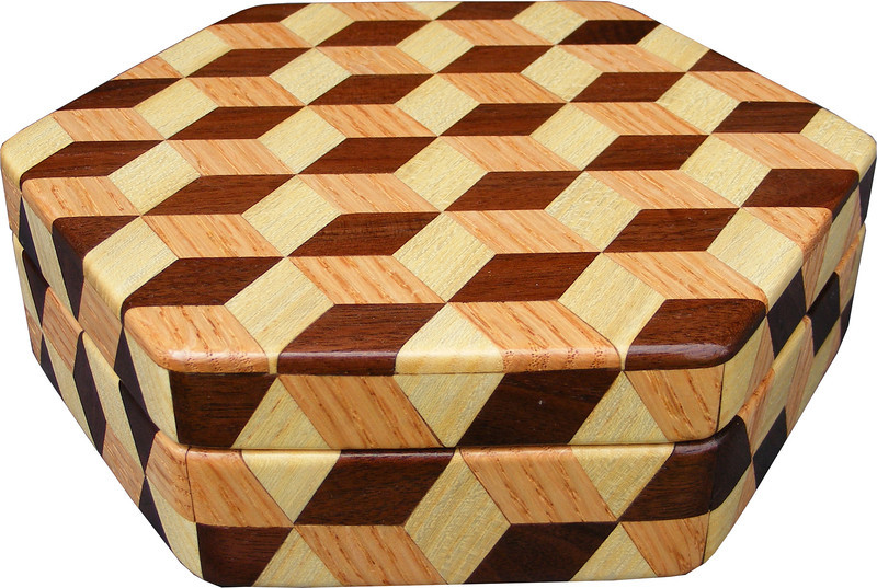 """Medium Hexagon Tumbling Block Box, view 1<br /> The medium hexagon box Tumbling Block is based on the """"Tumbling Block"""" quilt pattern. It measures 7 ¼"""" X 8 3/8"""" and 2 3/8"""" high. Inside measurements are 6 ¼"""" X 7"""" X 1 ½"""".  There are 198 pieces on the overlay. The pieces are cut and glued in place, one piece at a time. The pattern covers the top and extends over the edge uninterrupted, to the bottom. The box is finished in its natural color with 5 or 6 coats of a clear wiping varnish, rubbed in by hand. The pieces are a bit over 3/16"""" thick, glued onto a Baltic Birch base.<br /> <br /> This box is made from Hackberry, Oak, and Walnut, all native to Missouri. I lined the box with black velveteen.<br /> <br /> The pattern has the illusion of a lot of blocks but there are as many stars as there are blocks. The design forces you to see the blocks. On each diamond, if you go to the side you are in the middle of a block. At each point you are in the middle of a star that has 6 points."""