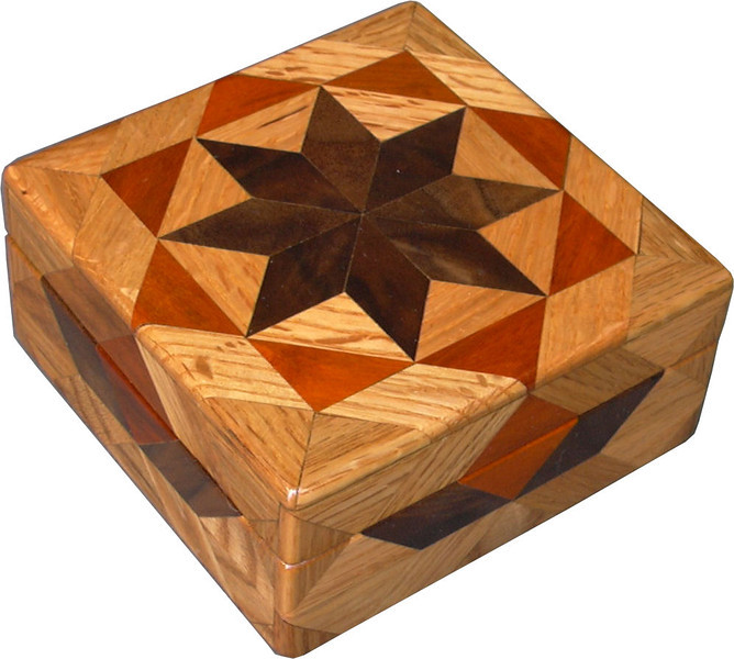 "Oak Square Box<br />  I call this my Square ""Oak"" Box. On the top of the box is a variation of a ""Rolling Star"" quilt pattern. The square box is about 5"" x 5"" and 2 1/2"" high on the outside. Inside it is 4"" x 4"" x 1 1/2"".  I made it using 116 pieces of wood cut in either diamond or triangle shapes from different kinds of wood. The box is finished in its natural color with 5 or 6 coats of a clear wiping varnish, rubbed in by hand. The pieces are a bit over 3/16"" thick, glued onto a Baltic Birch base, so they hold up much better than a thin veneer.<br />    The type of wood is listed on the bottom of the box from the center out. On this box the wood is ""Walnut"" and ""Oak"" from Missouri and ""Brazilwood"" from Brazil.<br />    On the bottom I signed it, listed the wood, and dated it.  After the date, the words ""Foot Cut"" let you know I made it on a foot powered table saw.<br />    I lined the box with black velveteen."
