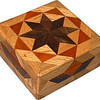 """Oak Square Box<br />  I call this my Square """"Oak"""" Box. On the top of the box is a variation of a """"Rolling Star"""" quilt pattern. The square box is about 5"""" x 5"""" and 2 1/2"""" high on the outside. Inside it is 4"""" x 4"""" x 1 1/2"""".  I made it using 116 pieces of wood cut in either diamond or triangle shapes from different kinds of wood. The box is finished in its natural color with 5 or 6 coats of a clear wiping varnish, rubbed in by hand. The pieces are a bit over 3/16"""" thick, glued onto a Baltic Birch base, so they hold up much better than a thin veneer.<br />    The type of wood is listed on the bottom of the box from the center out. On this box the wood is """"Walnut"""" and """"Oak"""" from Missouri and """"Brazilwood"""" from Brazil.<br />    On the bottom I signed it, listed the wood, and dated it.  After the date, the words """"Foot Cut"""" let you know I made it on a foot powered table saw.<br />    I lined the box with black velveteen."""