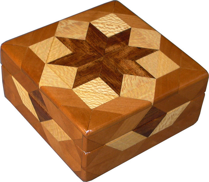 "Cherry Square Box<br />  I call this my ""Cherry"" Square Box. On the top of the box is a ""Rolling Star"" quilt pattern. The square box is about 5"" x 5"" and 2 1/2"" high on the outside. Inside it is 4"" x 4"" x 1 1/2"".  I made it using 116 pieces of wood cut in either diamond or triangle shapes from different kinds of wood. The box is finished in its natural color with 5 or 6 coats of a clear wiping varnish, rubbed in by hand. The pieces are a bit over 3/16"" thick, glued onto a Baltic Birch base, so they hold up much better than a thin veneer.<br />   The type of wood is listed on the bottom of the box from the center out. On this box the wood is ""Chechen"" from Mexico, ""Sycamore"" and ""Cherry"" from Missouri,<br />    On the bottom I signed it, listed the wood, and dated it.  After the date, the words ""Foot Cut"" let you know I made it on a foot powered table saw.<br /> <br />    I lined the box with black velveteen."