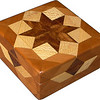 """Cherry Square Box<br />  I call this my """"Cherry"""" Square Box. On the top of the box is a """"Rolling Star"""" quilt pattern. The square box is about 5"""" x 5"""" and 2 1/2"""" high on the outside. Inside it is 4"""" x 4"""" x 1 1/2"""".  I made it using 116 pieces of wood cut in either diamond or triangle shapes from different kinds of wood. The box is finished in its natural color with 5 or 6 coats of a clear wiping varnish, rubbed in by hand. The pieces are a bit over 3/16"""" thick, glued onto a Baltic Birch base, so they hold up much better than a thin veneer.<br />   The type of wood is listed on the bottom of the box from the center out. On this box the wood is """"Chechen"""" from Mexico, """"Sycamore"""" and """"Cherry"""" from Missouri,<br />    On the bottom I signed it, listed the wood, and dated it.  After the date, the words """"Foot Cut"""" let you know I made it on a foot powered table saw.<br /> <br />    I lined the box with black velveteen."""