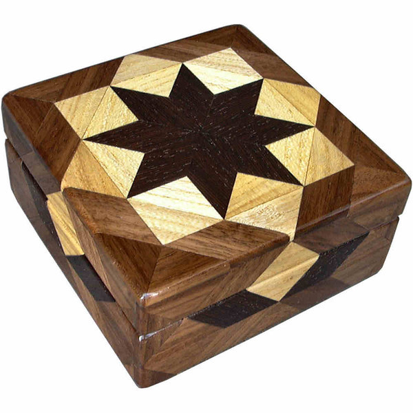 """Hackberry Square Box<br />  I call this my Square """"Hackberry"""" Box. On the top of the box is a """"Rolling Star"""" quilt pattern. The square box is about 5"""" x 5"""" and 2 1/2"""" high on the outside. Inside it is 4"""" x 4"""" x 1 1/2"""".  I made it using 116 pieces of wood cut in either diamond or triangle shapes from different kinds of wood. The box is finished in its natural color with 5 or 6 coats of a clear wiping varnish, rubbed in by hand. The pieces are a bit over 3/16"""" thick, glued onto a Baltic Birch base, so they hold up much better than a thin veneer.<br />   The type of wood is listed on the bottom of the box from the center out. On this box the wood is """"Wenge"""" from West Africa, """"Hackberry"""" and """"Walnut"""" from Missouri.<br />  <br />   On the bottom I signed it, listed the wood, and dated it.  After the date, the words """"Foot Cut"""" let you know I made it on a foot powered table saw.<br />  <br />   I lined the box with black velveteen."""