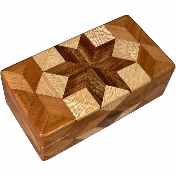 """Cherry Glasses Box<br /> I call this my """"Cherry"""" Glasses Box. On the top of the box is a variation of a """"Rolling Star"""" quilt pattern.  The glasses box is about 3 1/2"""" x 6 1/2"""" and 2 1/4"""" high on the outside. Inside it is 2 3/8"""" x 5 3/8"""" x 1 1/2"""".  I made it using 116 pieces of wood cut in either diamond or triangle shapes from different kinds of wood. The box is finished in its natural color with 5 or 6 coats of a clear wiping varnish, rubbed in by hand. The pieces are a bit over 3/16"""" thick, glued onto a Baltic Birch base, so hold up much better than a thin veneer.<br /> The type of wood is listed on the bottom of the box from the center out. On this box the wood is """"Chechen"""" from Mexico, """"Sycamore"""" and """"Cherry"""" from Missouri.<br />    On the bottom I signed it, listed the wood, and dated it.  After the date, the words """"Foot Cut"""" let you know I made it on a foot powered table saw.<br />  <br /> I lined the box with black velveteen."""