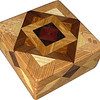 """High Aunt Sukeys Choice Square Box<br />    I call this my """"Aunt Sukeys Choice High Oak"""" Square Box. On the top of the box is an """"Aunt Sukeys Choice"""" quilt pattern.  The square box is about 5"""" x 5"""" and 2 3/8"""" high on the outside. Inside it is 3 3/4"""" x 3 3/4"""" x 1 1/2"""".  I made it using 140 pieces of wood cut in either diamond or triangle shapes from different kinds of wood. The box is finished in its natural color with 5 or 6 coats of a clear wiping varnish, rubbed in by hand. The pieces are a bit over 3/16"""" thick, glued onto a Baltic Birch base, so they hold up much better than a thin veneer.<br />    The type of wood is listed on the bottom of the box from the center out. On this box the wood is """"Purpleheart"""" from Central or South America, """"Wenge"""" from West Africa, """"Satinwood"""" from Sri Lanka, """"Lacewood"""" from Australia, """"Walnut,  Hackberry, and Oak"""" from Missouri.<br />     On the bottom I signed it, listed the wood, and dated it.  After the date, the words """"Foot Cut"""" let you know I made it on a foot powered table saw.<br />  <br />    I lined the box with black velveteen."""