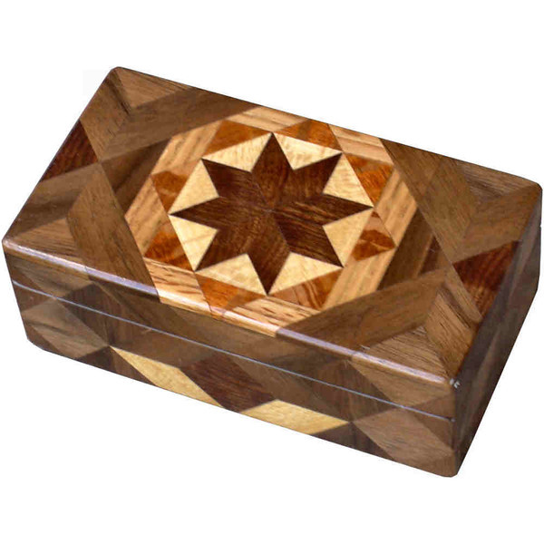 """Glasses Box Brown Tone<br />   I call this my """"Brown Tone"""" Glasses Box. On the top of the box is a variation of a """"Rolling Star"""" quilt pattern.  The glasses box is about 3 1/2"""" x 6 1/2"""" and 2 1/4"""" high on the outside. Inside it is 2 3/8"""" x 5 3/8"""" x 1 1/2"""".  I made it using 132 pieces of wood cut in either diamond or triangle shapes from different kinds of wood. I used the half size pieces to make the """"Rolling Star"""" pattern on top so there are 32 pieces where there would normally be only 16 pieces. The box is finished in its natural color with 5 or 6 coats of a clear wiping varnish, rubbed in by hand. The pieces are a bit over 3/16"""" thick, glued onto a Baltic Birch base, so they hold up much better than a thin veneer.<br />   The type of wood is listed on the bottom of the box from the center out. On this box the wood is """"Chechen"""" from Mexico, """"Sycamore"""" from Missouri, """"Lacewood"""" from Australia, """"Oak"""" and """"Walnut"""" from Missouri.<br />   I made this box in 1997. On the bottom I signed it, listed the wood, and dated it.  After the date, the words """"Foot Cut"""" let you know I made it on a foot powered table saw.<br />  <br />   I lined the box with black velveteen."""
